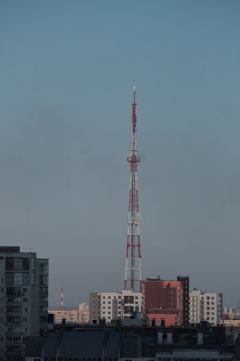 Communications tower and buildings against clear sky