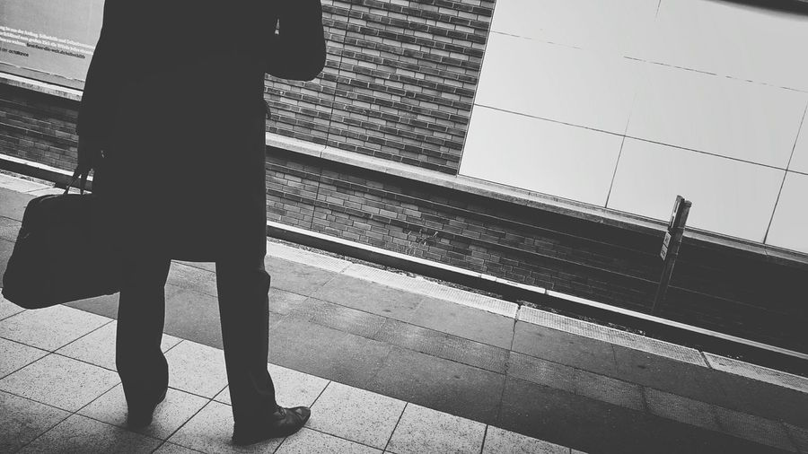 Low section of man with bag standing on railroad station platform