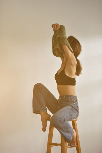 Young woman removing top while sitting on stool against white background