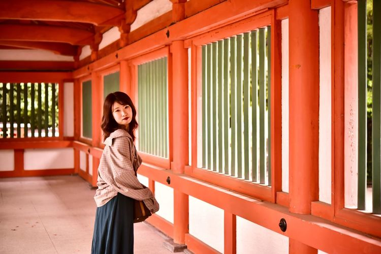 Portrait of smiling woman standing against shrine