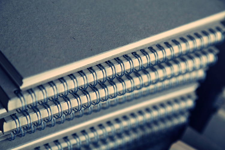 A pile of notebook paper Arrangement Close-up Connection Focus On Foreground High Angle View In A Row Indoors  Industry Large Group Of Objects Metal No People Order Pattern Repetition Selective Focus Still Life Technology Textured
