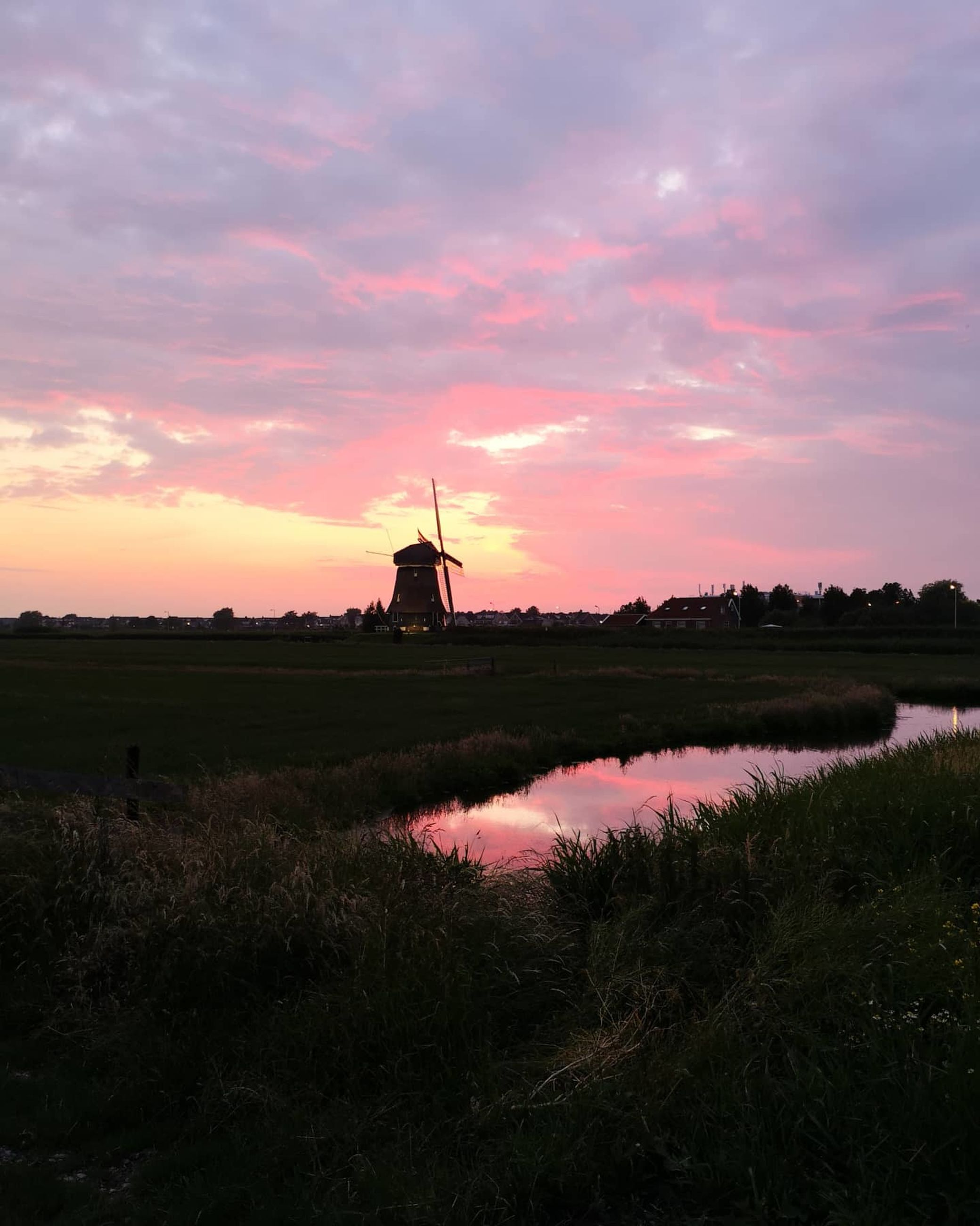 sky, environment, dawn, sunset, windmill, landscape, nature, cloud, horizon, environmental conservation, wind power, water, wind turbine, evening, turbine, beauty in nature, plant, architecture, rural scene, power generation, renewable energy, no people, scenics - nature, reflection, field, agriculture, afterglow, silhouette, land, alternative energy, built structure, tranquility, grass, outdoors, pink, tower, social issues, travel destinations, travel, traditional windmill, tranquil scene, mill, industry, technology, business finance and industry, lake