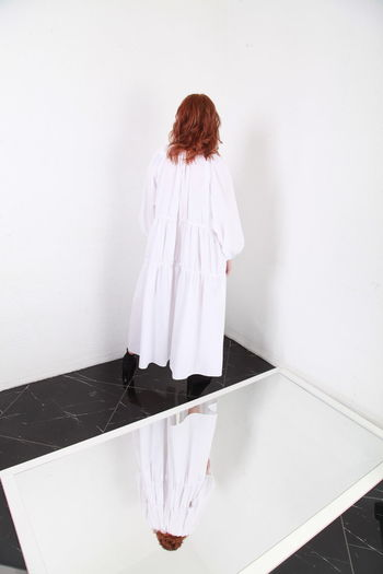 Rear view of woman standing on white table