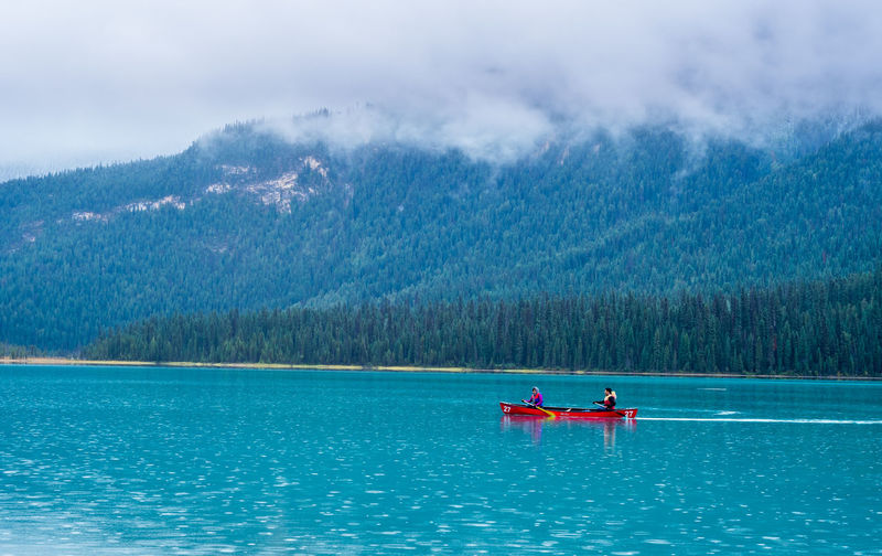 People In Boat On Lake Against Mountain