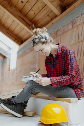 Woman working while sitting against wall