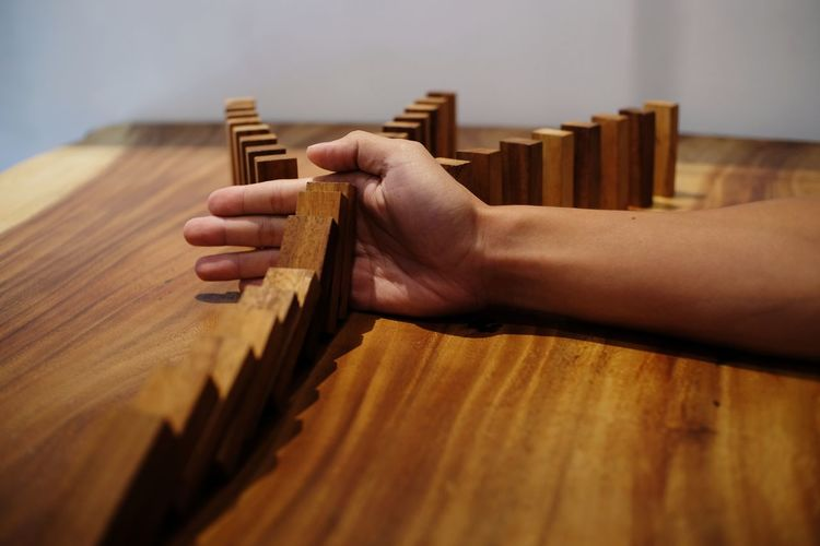 Cropped Image Of Man Stopping Dominoes On Table