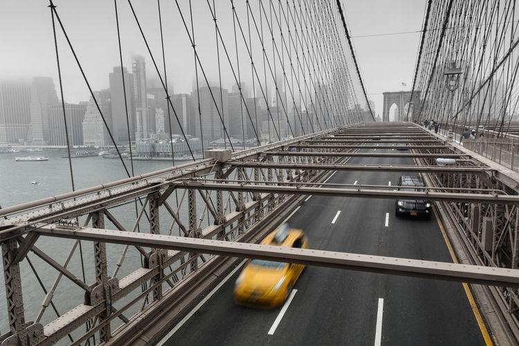 Suspension bridge against sky in city