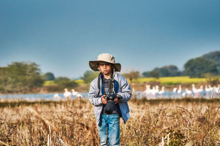 Portrait of boy holding camera standing on field against sky