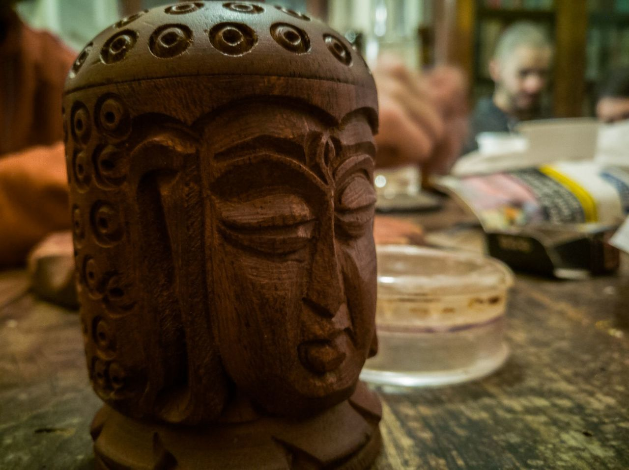 focus on foreground, close-up, religion, table, no people, indoors, sculpture, spirituality, statue, day