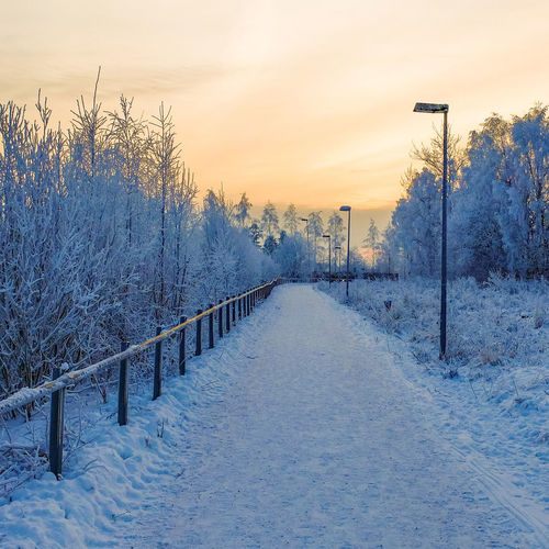 Snow covered road at sunset