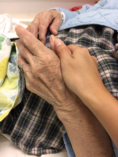 Cropped image of woman holding grandmother hands lying on bed