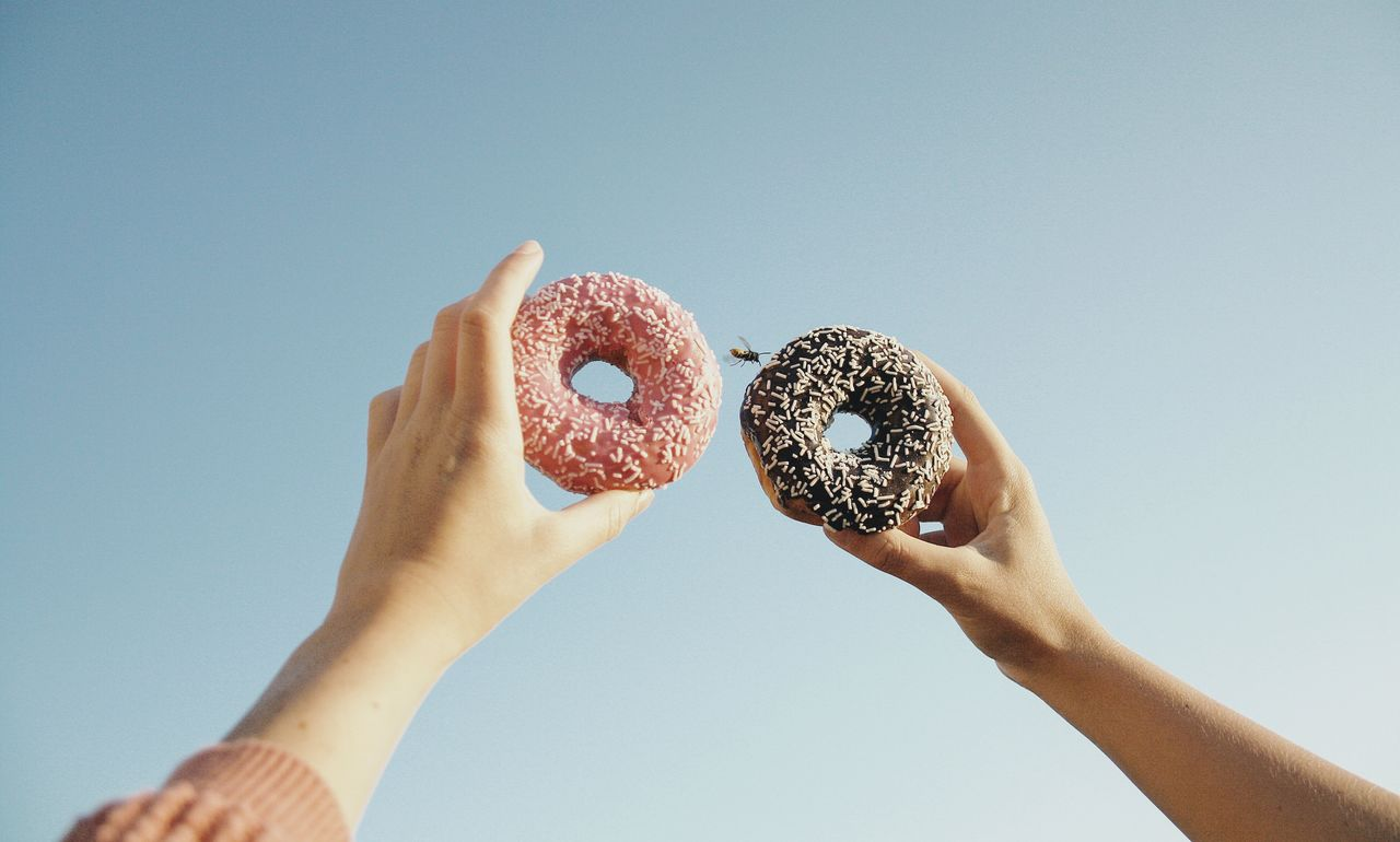 Cropped Image Of People Holding Donuts Against Clear Sky