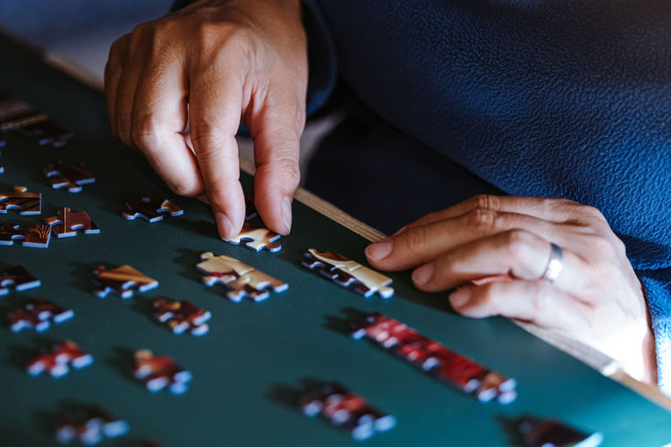 High angle view of woman playing with puzzle