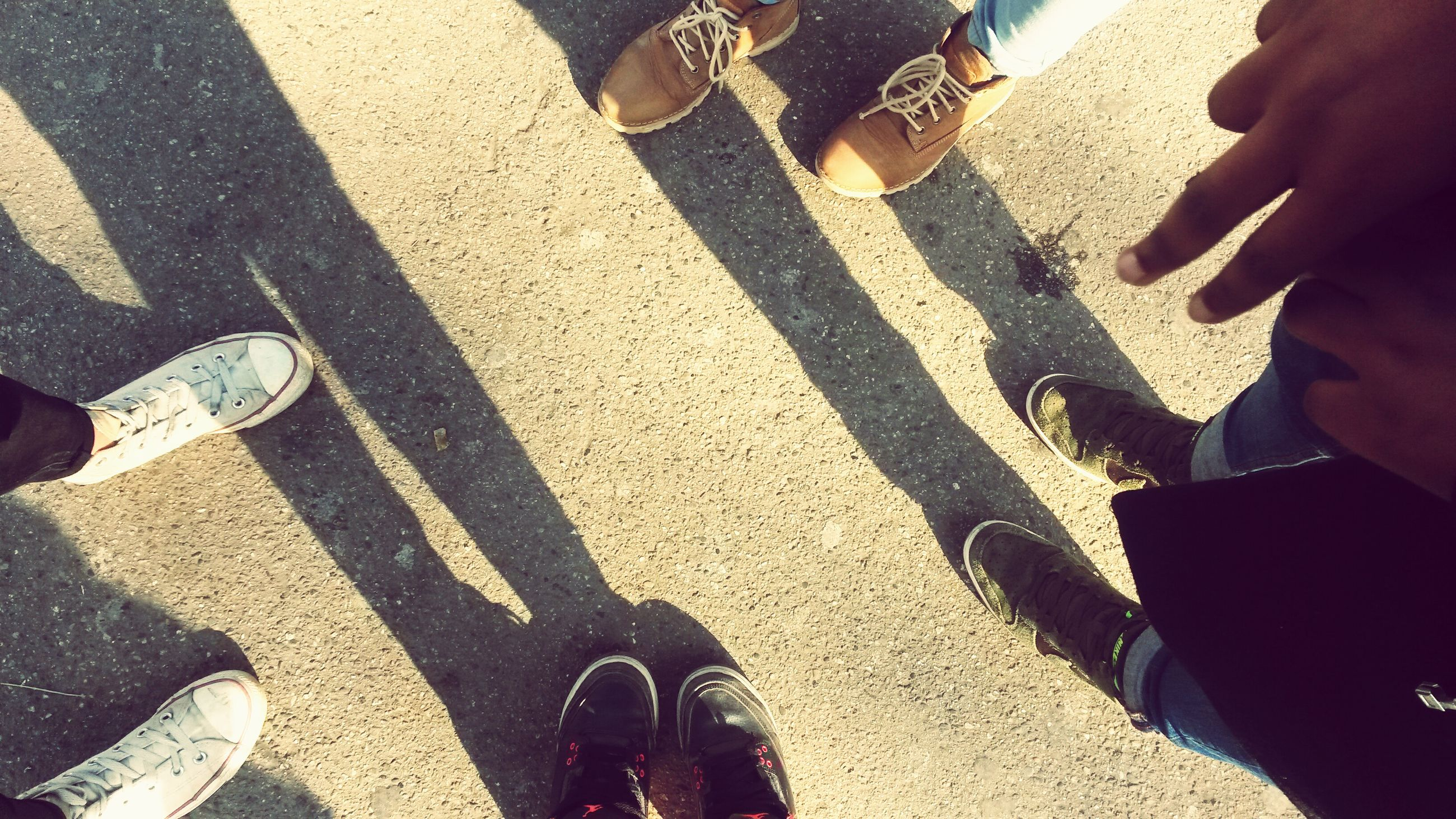 low section, lifestyles, person, leisure activity, men, togetherness, standing, high angle view, human foot, bonding, friendship, shadow, personal perspective, part of