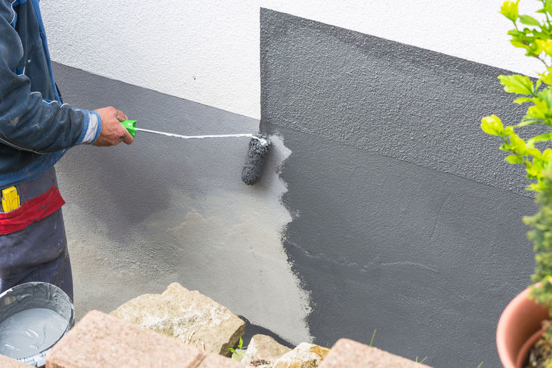 Close-up, arm of a house painter with paint roller in hand painting a house wall with gray paint. Adult Adults Only Day Holding Human Body Part Human Hand Low Section Manual Worker Men One Man Only One Person Only Men Outdoors People Real People Spraying
