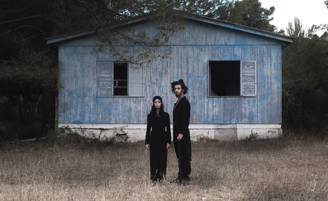 Portrait of couple standing by old building