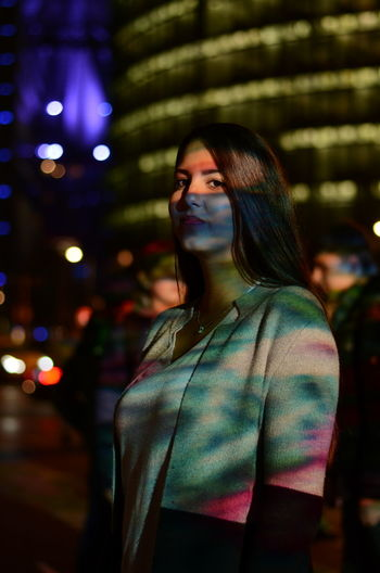Young woman standing in illuminated city at night