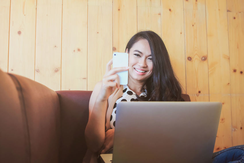 Business beautiful woman using smart phone and laptop on cozy couch Asian  Beautiful Casual Clothing Communication Computer Connection Couch Happiness Holding Indoors  Laptop Leisure Activity Lifestyles Mobile Phone One Person One Woman Only Portable Information Device Sitting Smart Phone Smiling Technology Wireless Technology Women Wood - Material Working