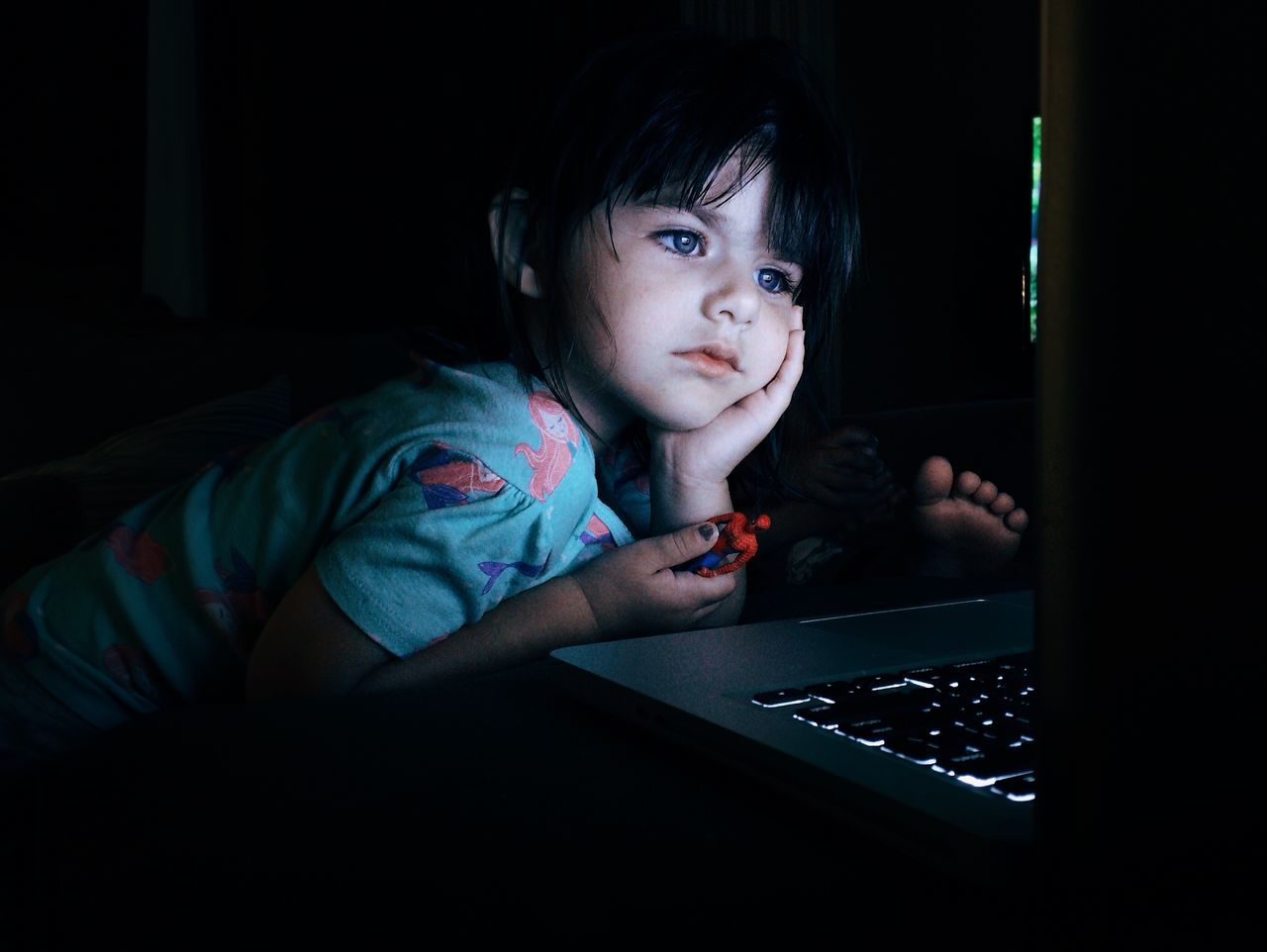 Girl with hand on chin looking at laptop