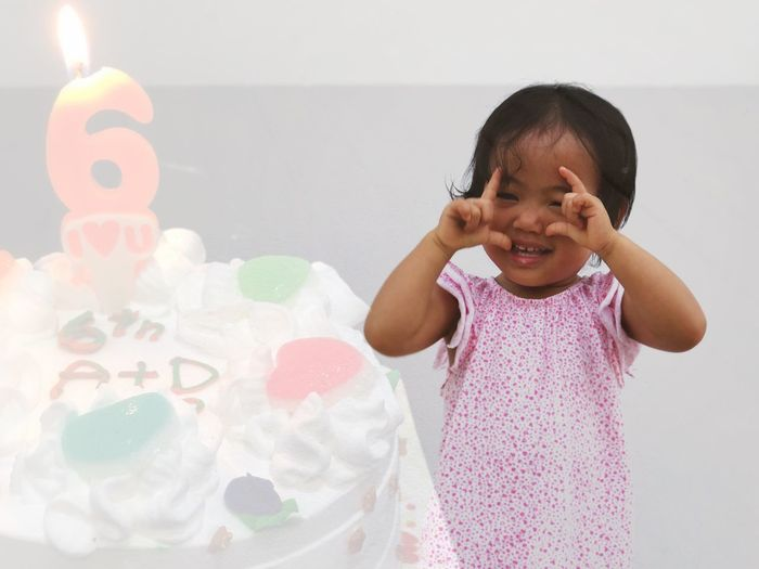 Digital composite image of girl by birthday cake