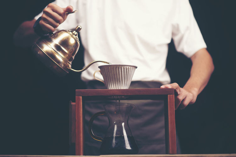 Midsection Of Man Pouring Black Coffee In Mug