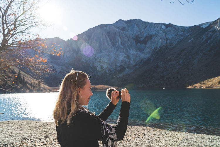 Blonde haired woman at beautiful mountain lake filming with video camera as sun begins to set