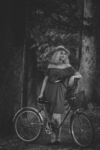 Full length of woman standing with bicycle against trees in forest