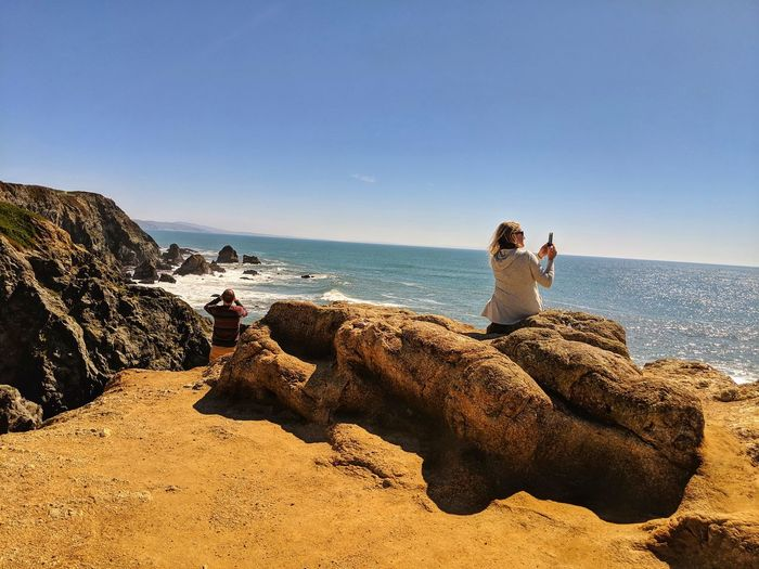 Smartphone photography. Woman. Man. Capturing the art of the ocean. Sandstone Smartphone Photography Photos Distance Headlands Golden Sky Boulders Dirt Water Sea Friendship Young Women Beach Togetherness Sitting Men Clear Sky Sand Tranquil Scene Idyllic Horizon Over Water Seascape Ocean Countryside Tranquility Remote Scenics Non-urban Scene