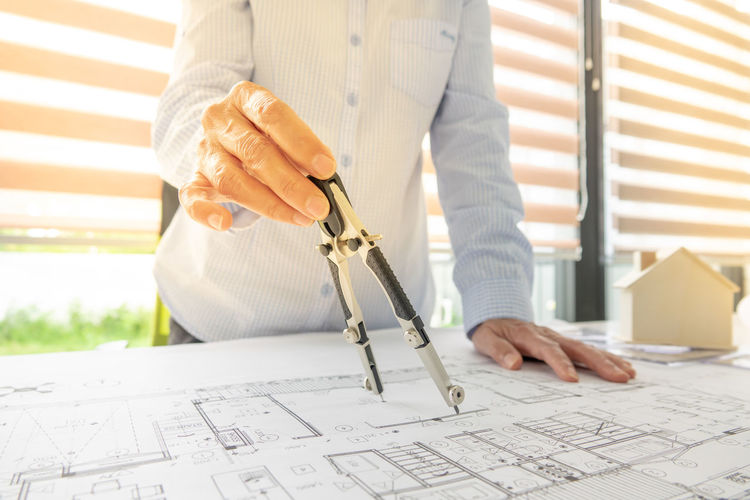 Midsection of female architect working on blueprint at desk in office