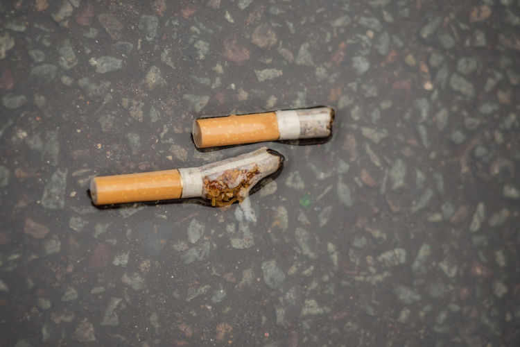 Close-up of wet cigarette on footpath