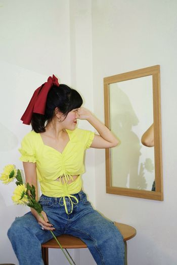 Woman holding umbrella while standing against wall at home