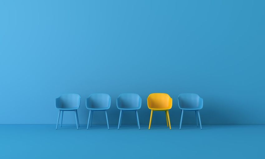 Empty chairs and table against blue wall