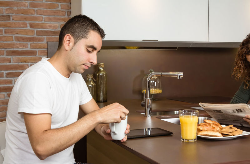 Tired young man holding cup of coffee at home breakfast while his wife reading news in the newspaper Family Fruit Girlfriend Thirties Relaxing Husband Boyfriend 30s Wife Relationship Adult Lifestyle Interior Love Cup Caucasian Healthy Two Coffee Glass Orange Girl Juice Meal Drink Together Young Woman Kitchen Man Indoors  Food Morning Technology Newspaper Digital Tablet News Read Problems Bored Tired Serious Male Home People Female Couple Breakfast