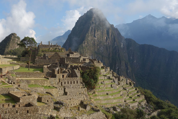 Mach picchu ruins of mountains against cloudy sky