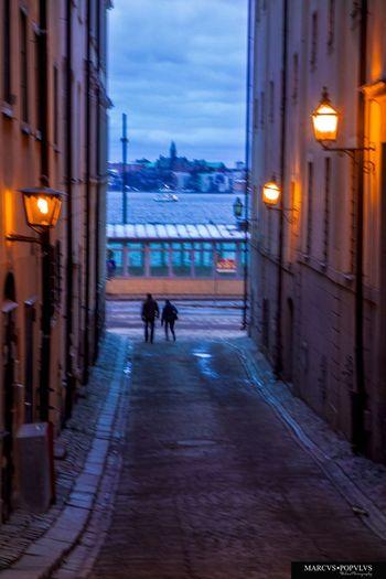 Título: Nunc aut numquam (Ahora o nunca) Autor: Marcus Populus Lugar: Stockholm Cámara: SONY DSC RX100 Punto F: f/4.9 Tiempo de exposición: 1/10s Velocidad ISO: 800 Distancia focal: 37mm Architecture Building Exterior City Illuminated Real People Street Light Walking