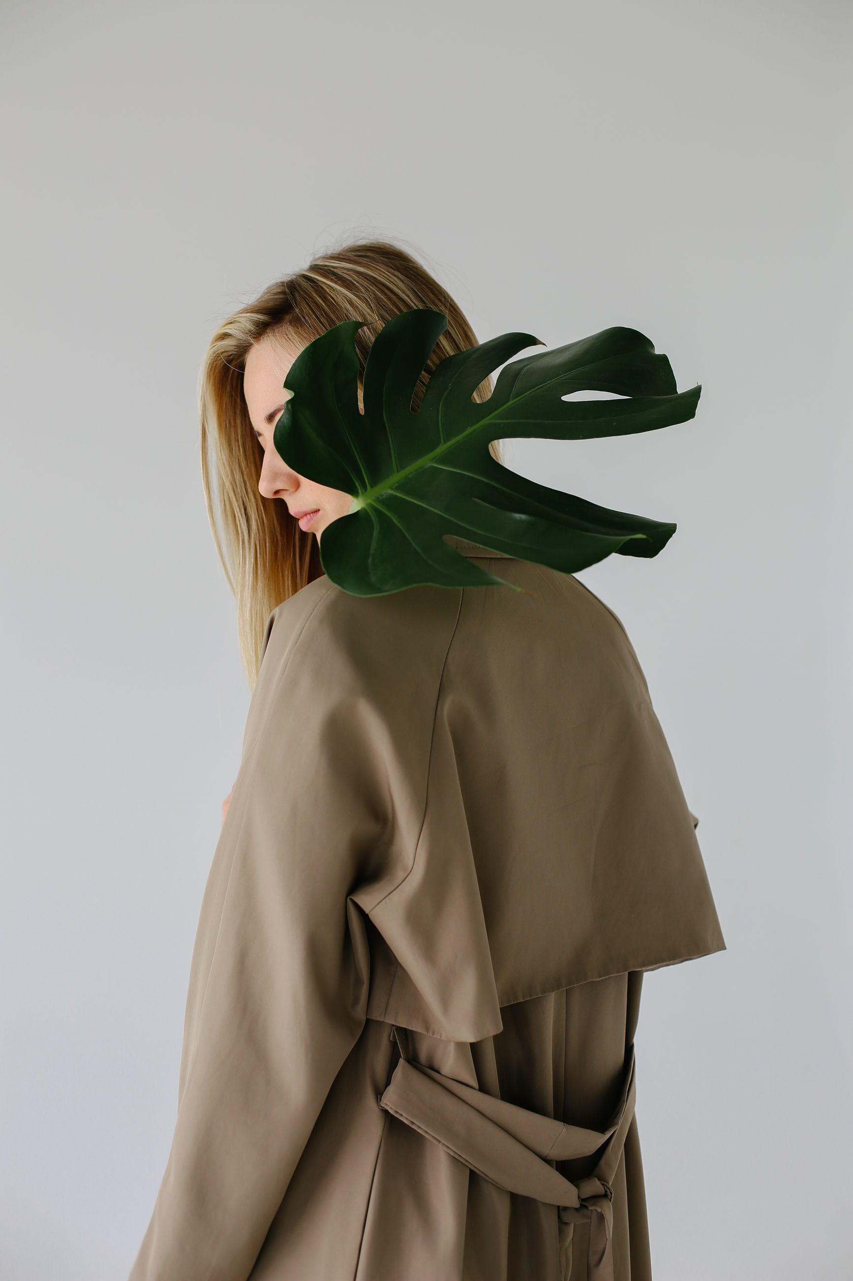 studio shot, one person, indoors, women, standing, adult, clothing, lifestyles, plant, white background, holding, rear view, hairstyle, young adult, hair, leisure activity, leaf, casual clothing, plant part, obscured face, scarf