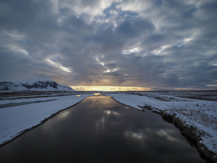 Scenic view of snow covered land against sky during winter