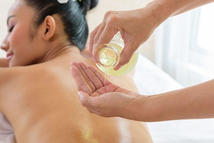 Cropped hands of masseuse giving massage with oil to young woman relaxing at spa