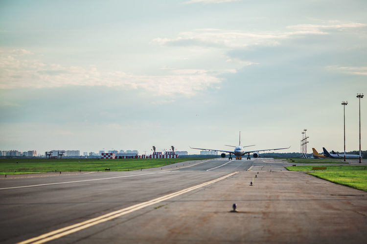 Airplane at airport runway against cloudy sky