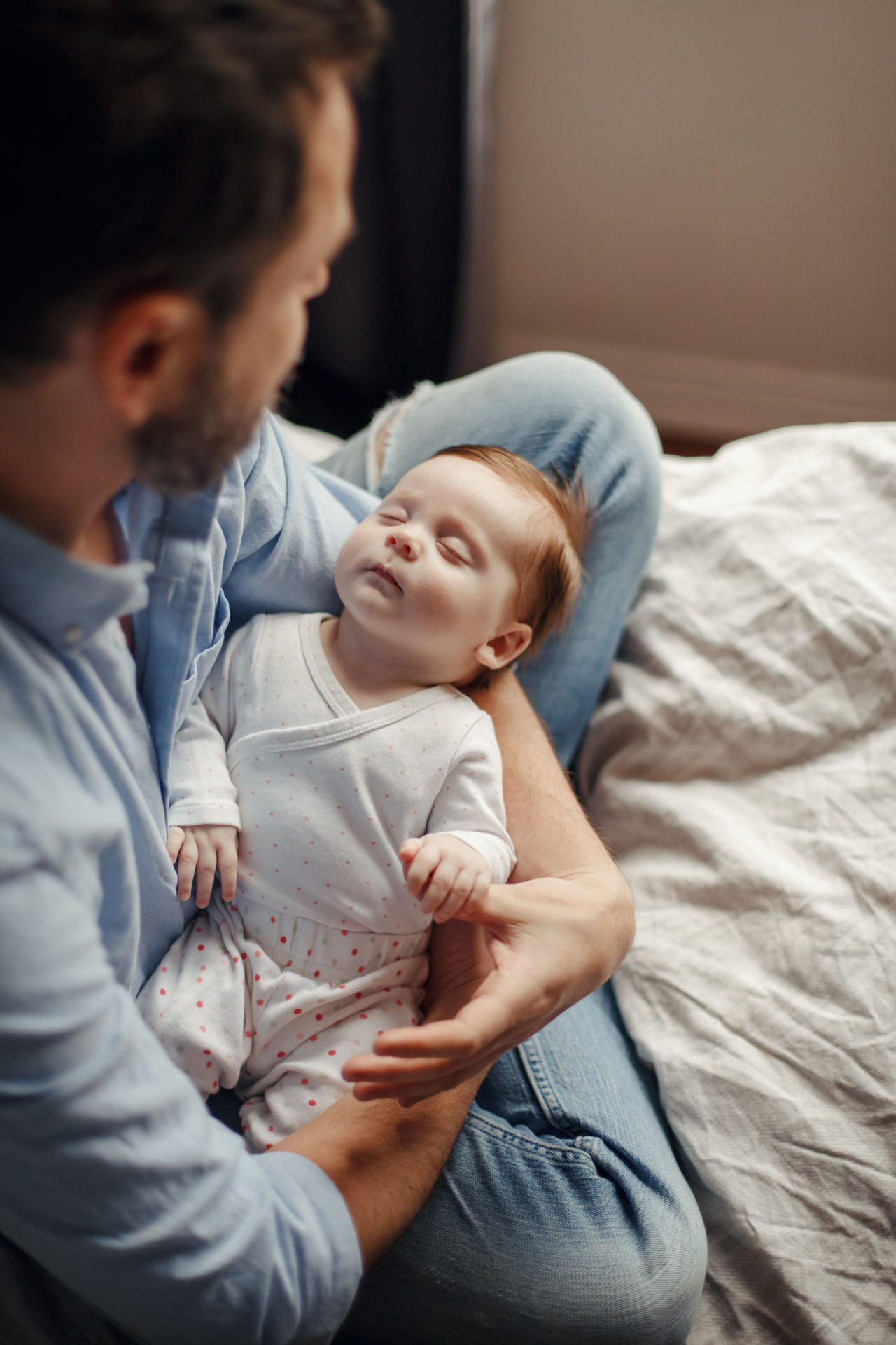 High angle view of father holding sleeping daughter while sitting on bed