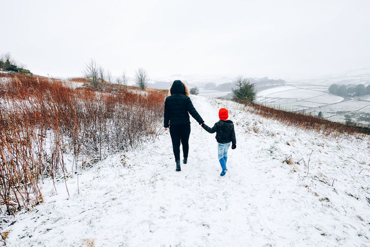 Adult and young boy holding hands while walking in the snow in West Yorkshire, United Kingdom Family Holding Hands United Kingdom Adult Adventure Beauty In Nature Bonding Cold Temperature Day Family With One Child Frozen Full Length Hiking Nature Outdoors People Real People Rear View Snow Snowing Togetherness Walking Warm Clothing West Yorkshire Winter