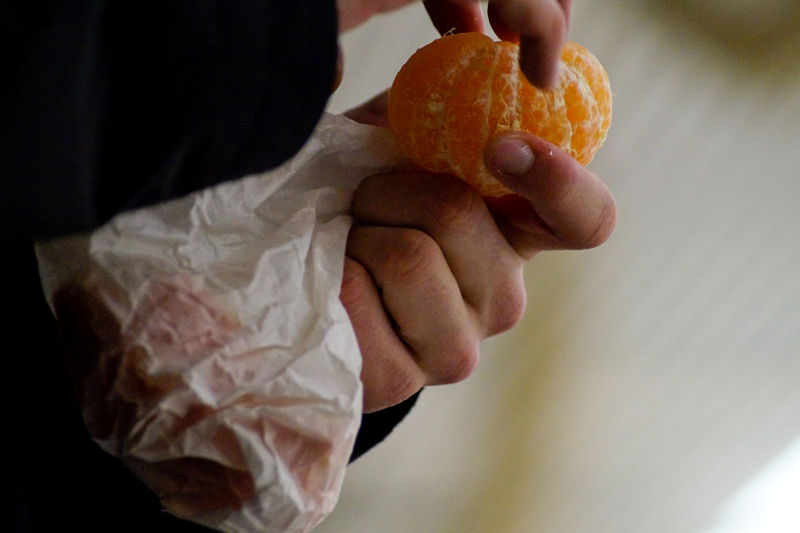 Cropped hand of person holding peeled orange