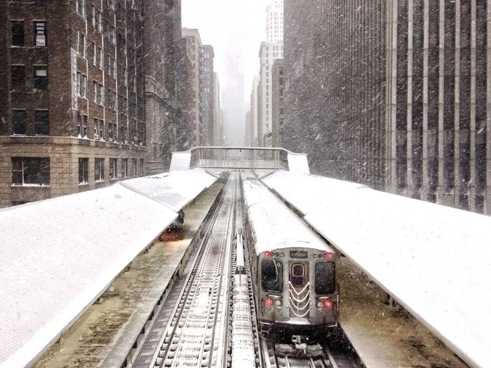 Railroad tracks amidst buildings in city during winter