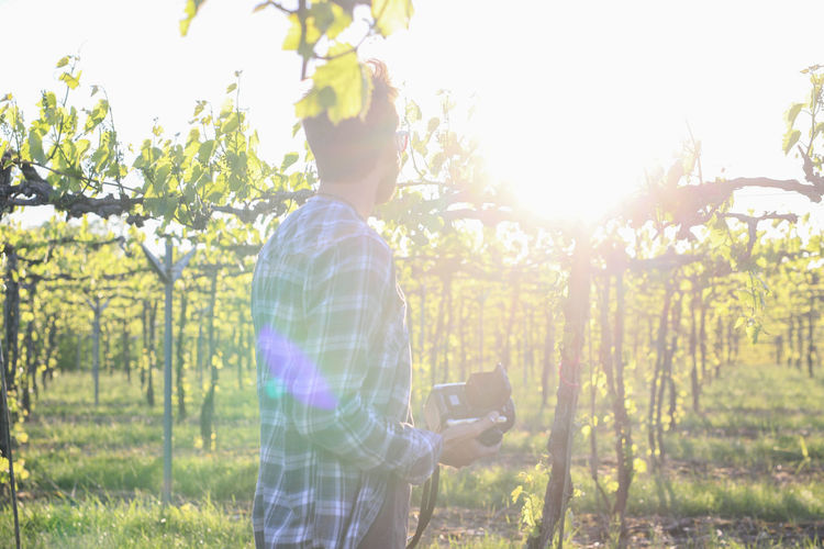 Adult Beauty In Nature Casual Clothing Communication Day Field Growth Holding Men Mobile Phone Nature One Person Outdoors People Portable Information Device Real People Rear View Standing Sunlight Technology Tree Vineyard Wine Wireless Technology Young Adult