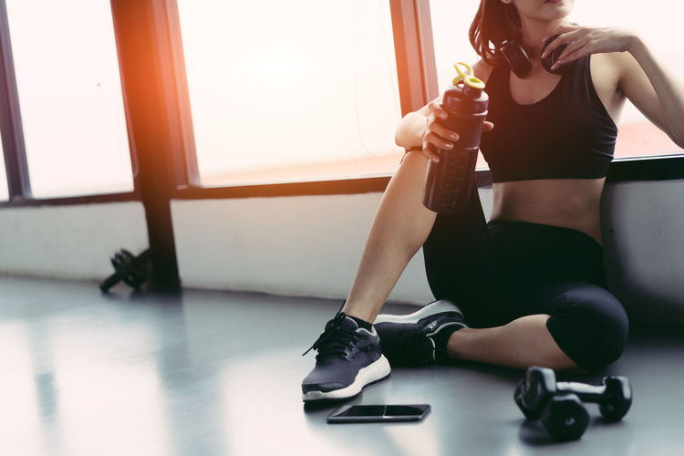Low Section Of Young Woman Having Protein Drink Against Window In Gym