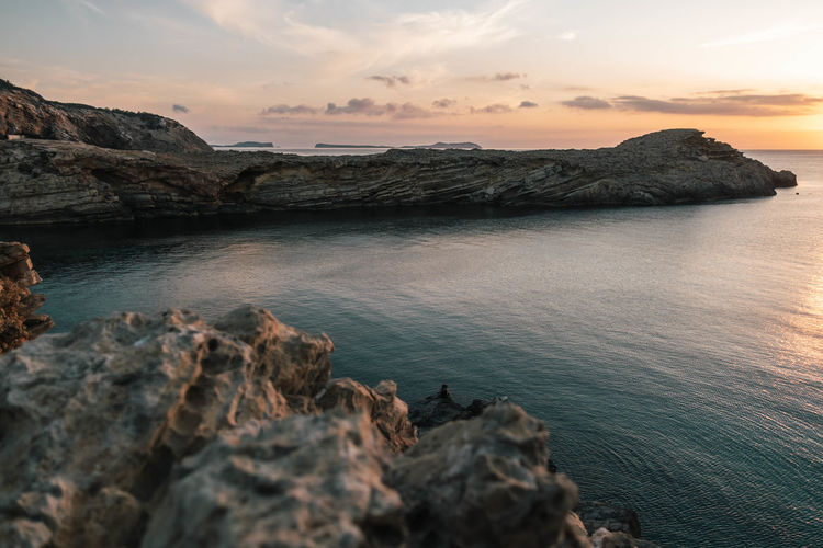 Rocky coastline by sea against sky during sunset