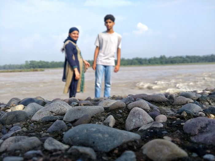 Mother and son standing at beach while stones in foreground