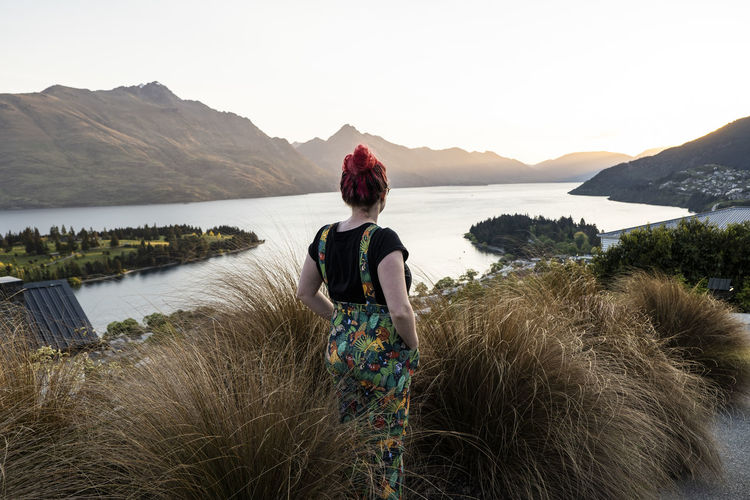 Rear view of woman looking at lake against mountain range