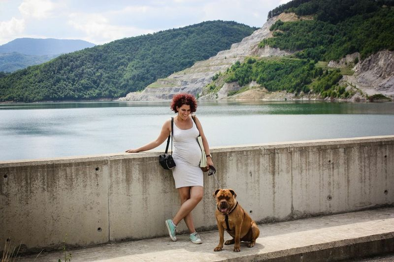 Smiling pregnant woman with dog standing on bridge over lake against mountains