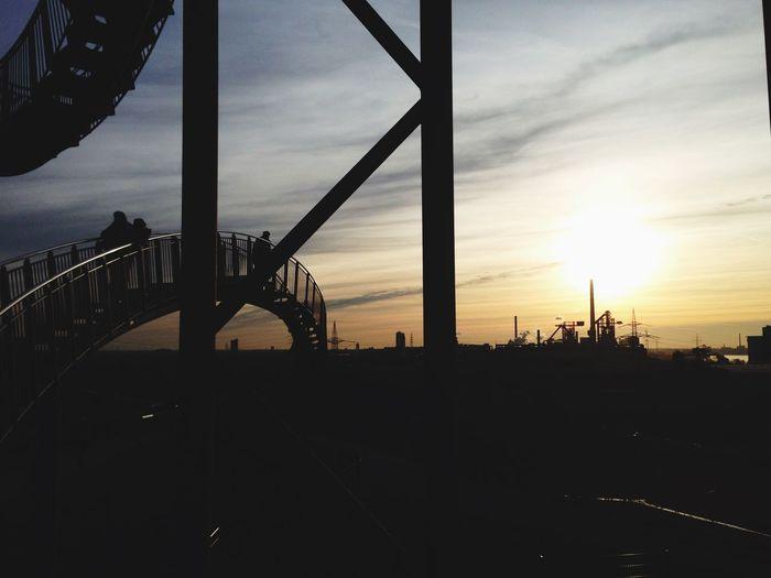 Silhouette bridge against cloudy sky